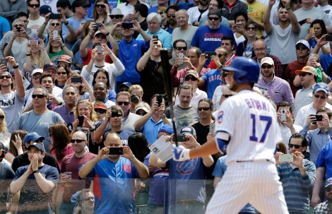Baseball fans take photos as Chicago Cubs' Kris Bryant bats during the first inning of a baseball game against the San Diego Padres in Chicago, Friday, April 17, 2015. (AP Photo/Nam Y. Huh)